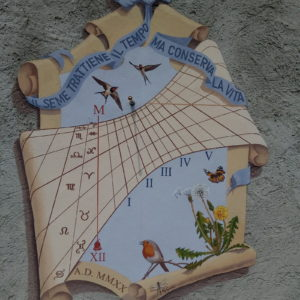 Meridiana dipinta su parete grezza color cemento. Sundial painted on rough concrete wall.